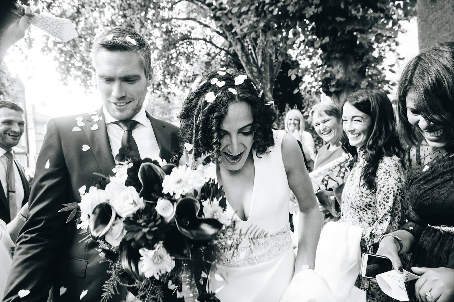 Black and white photography of wedding couple during confetti.